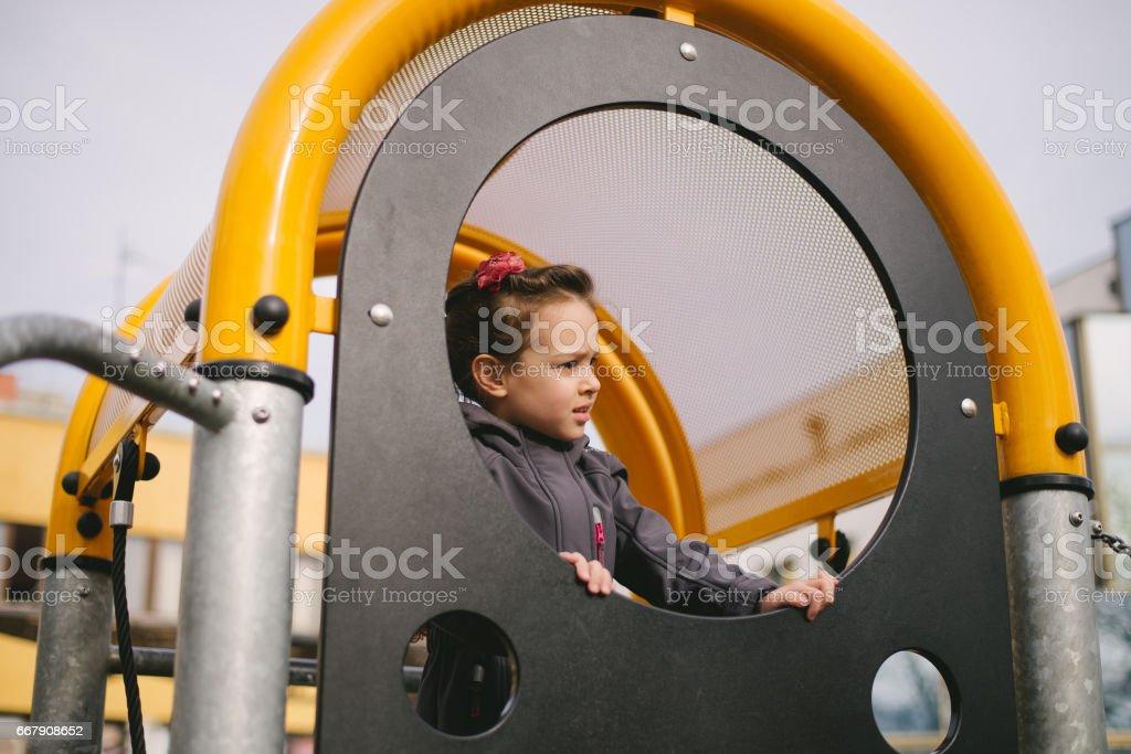 Little girl in the children's park having fun stock photo