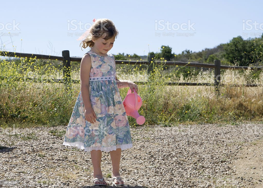 Little Girl in the Country with a Watering Can stock photo