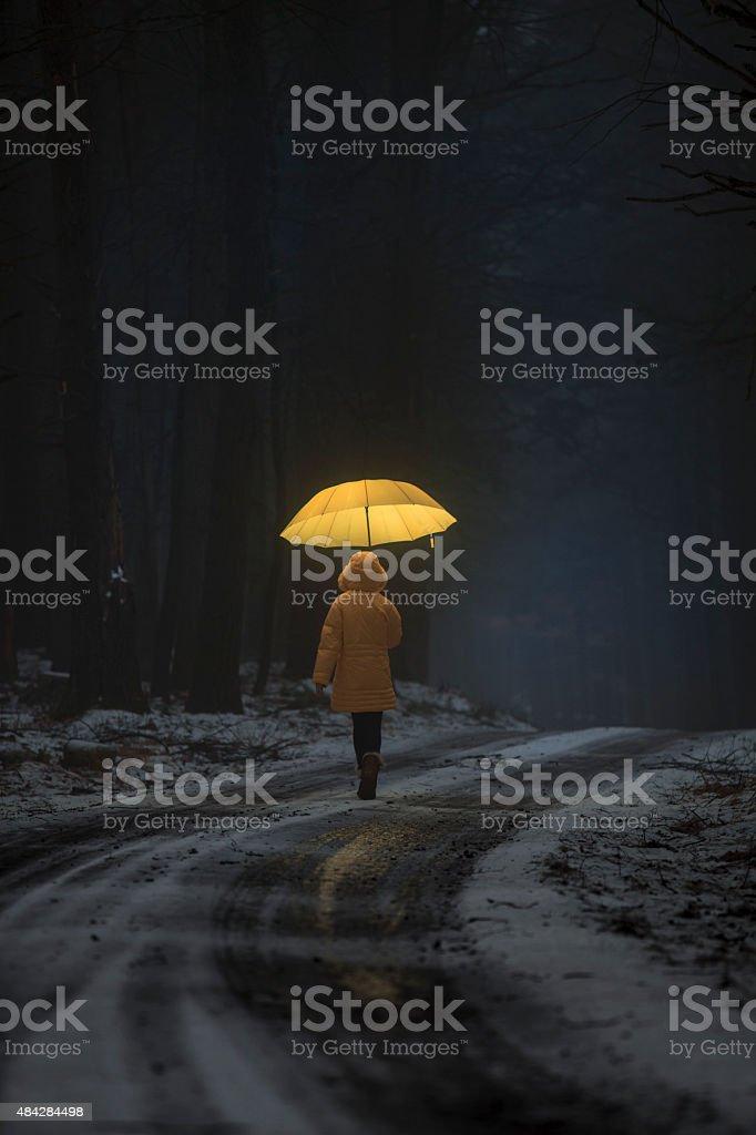 Little girl in the dark forest stock photo