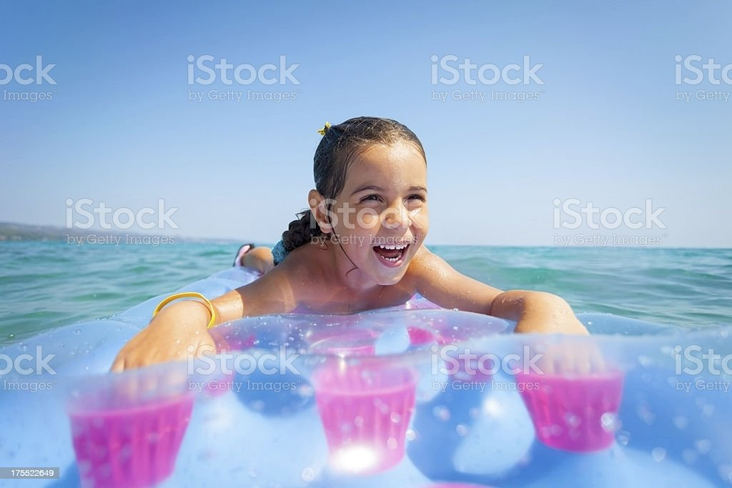 Little girl in the Sea lie on a beach mattress royalty-free stock photo