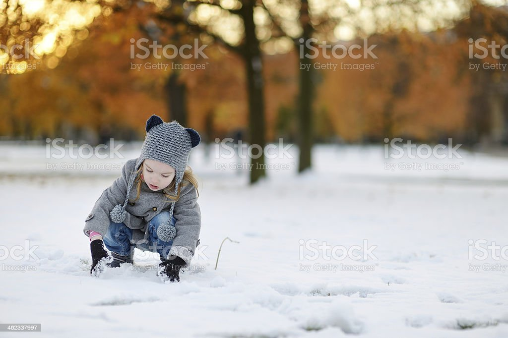 A little girl in winter clothing crouching in the snow royalty-free stock photo
