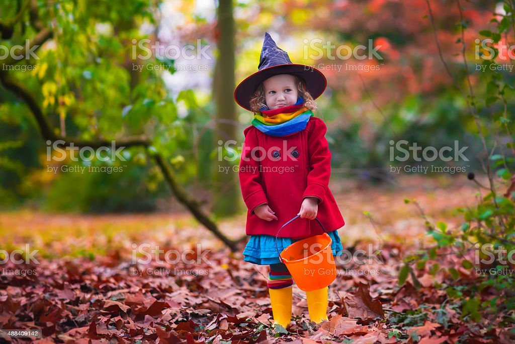 Little girl in witch costume at Halloween stock photo