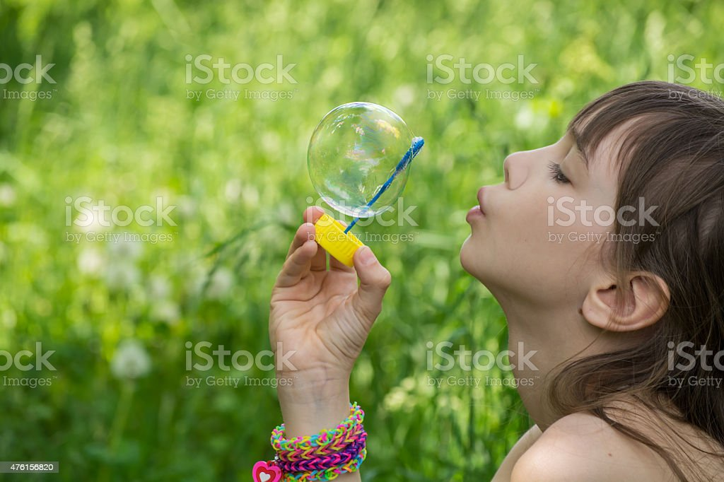 Little girl inflates soap bubbles in the park stock photo