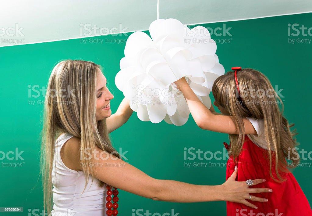 Little girl installing a light bulb royalty-free stock photo