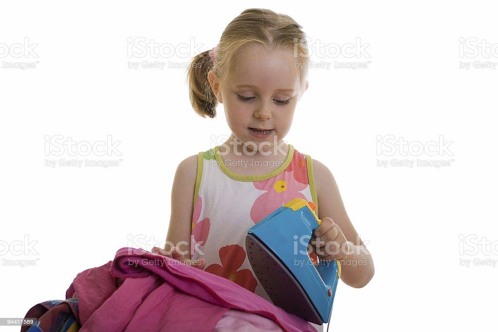 Little girl ironing dress stock photo
