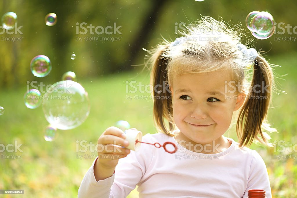 Little girl is blowing a soap bubbles stock photo