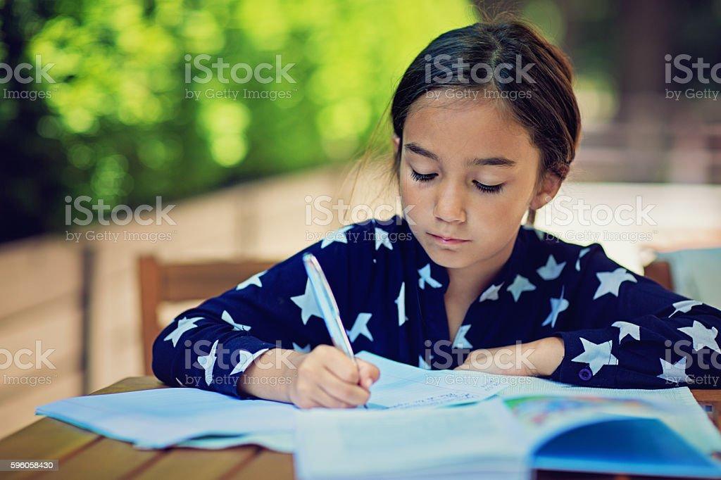 Little girl is doing her homework stock photo
