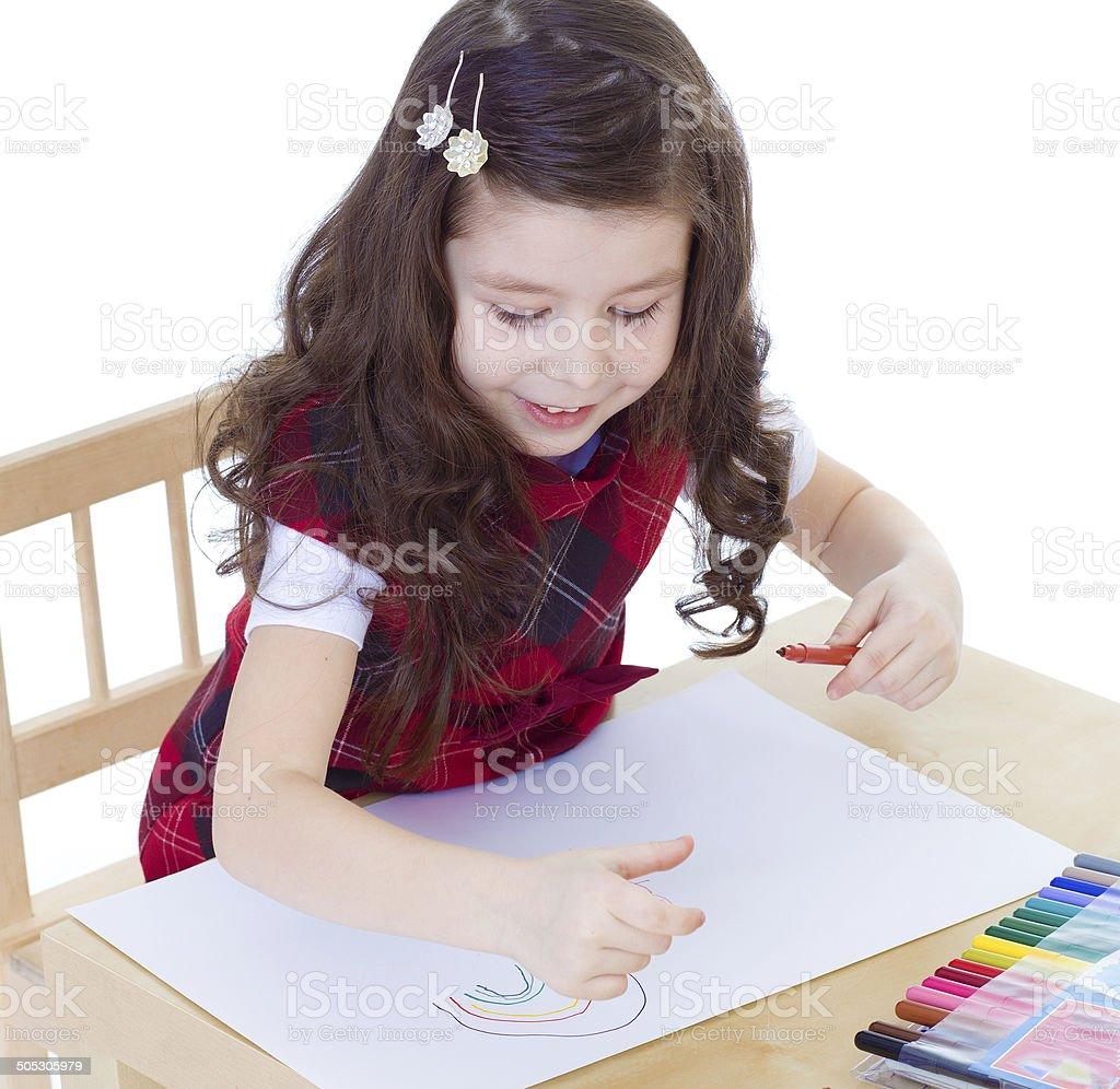 Petite fille, dessin avec des crayons de couleur et de repos photo libre de droits