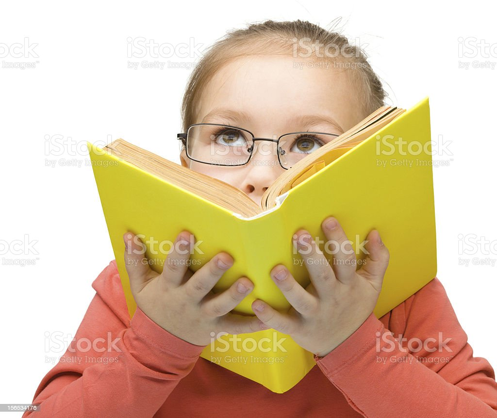 Little girl is dreaming while reading book royalty-free stock photo