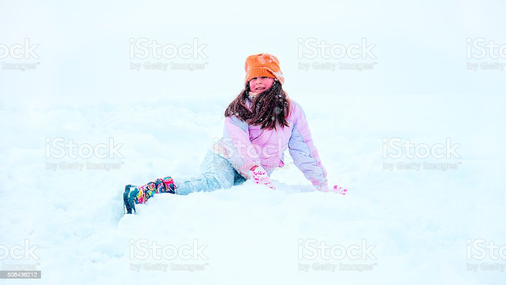 Little girl is happily rolling in the snow stock photo