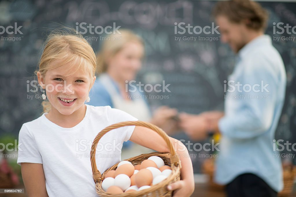 A little girl is holding a basket of fresh eggs to stock photo