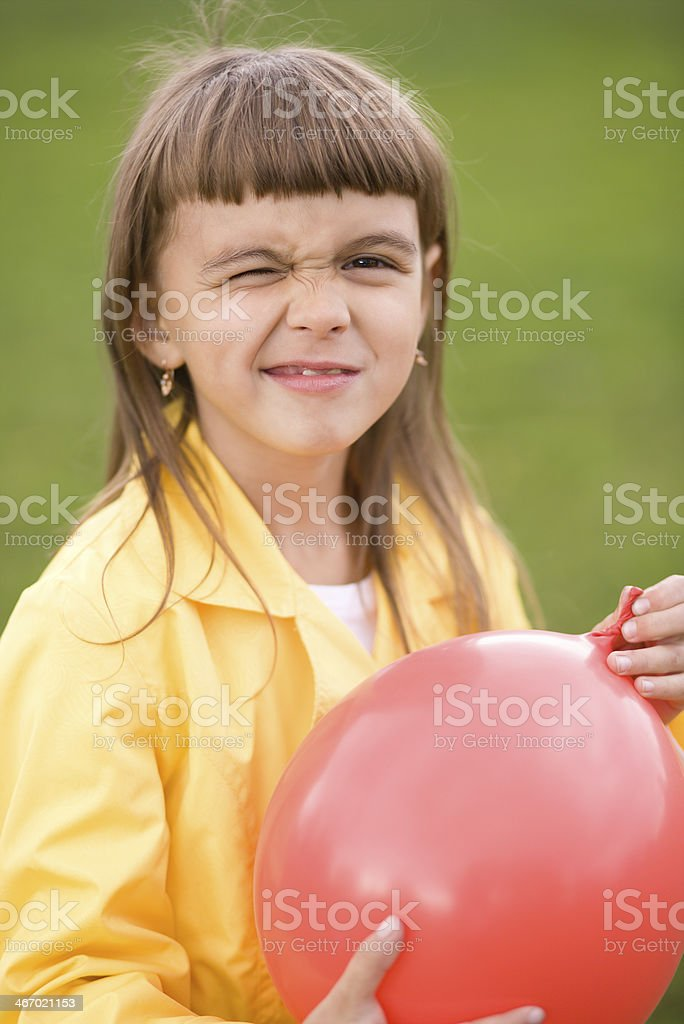 Little girl is inflating red balloon royalty-free stock photo
