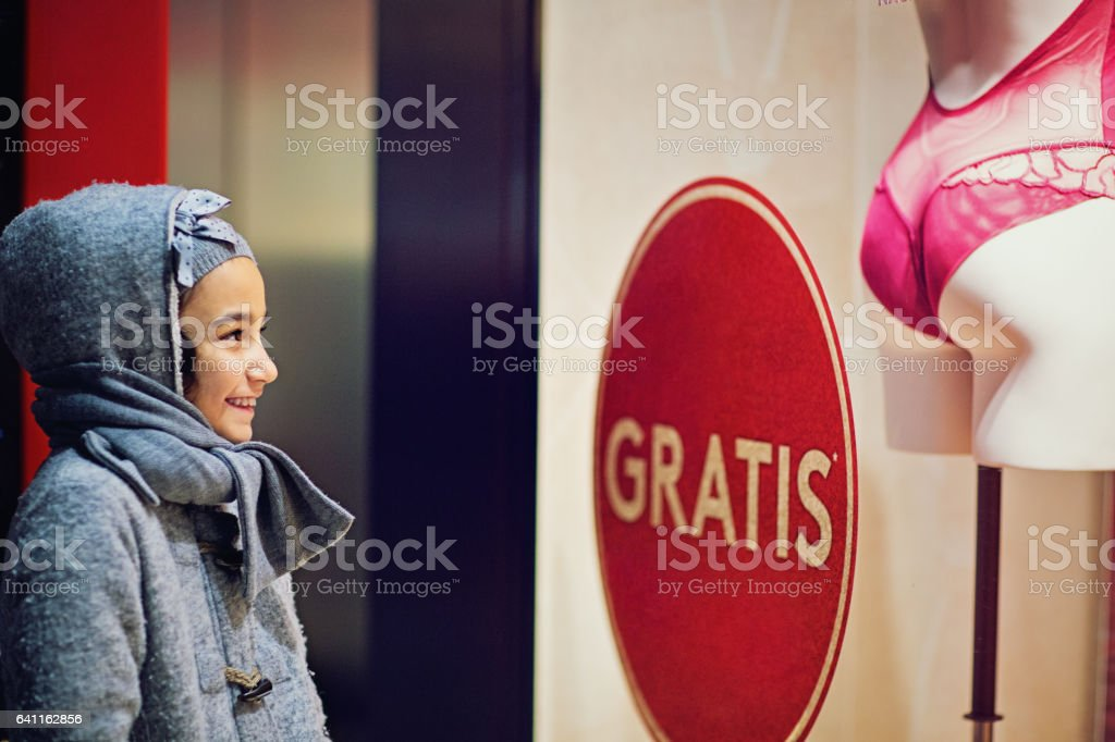 Little girl is looking a store window stock photo