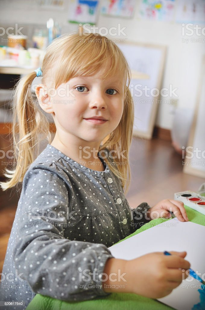 Little girl is painting in the artist's studio stock photo