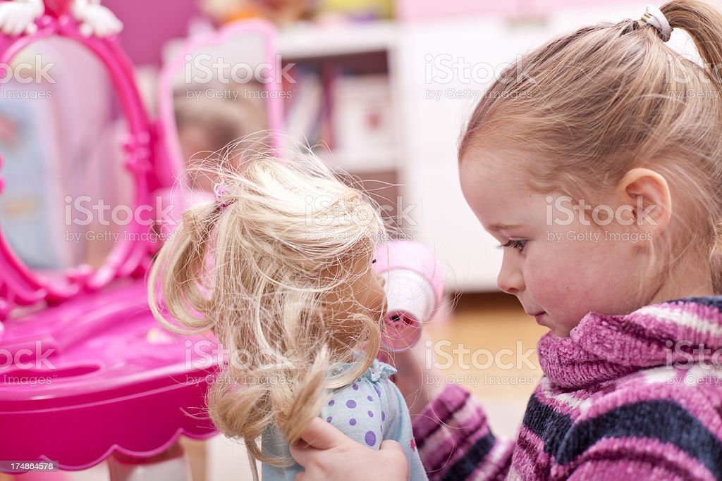 Little girl is playing with her doll stock photo