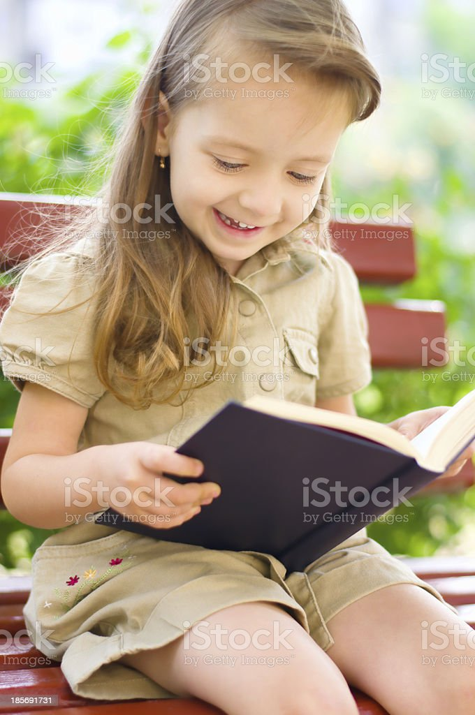 little girl is reading a book royalty-free stock photo
