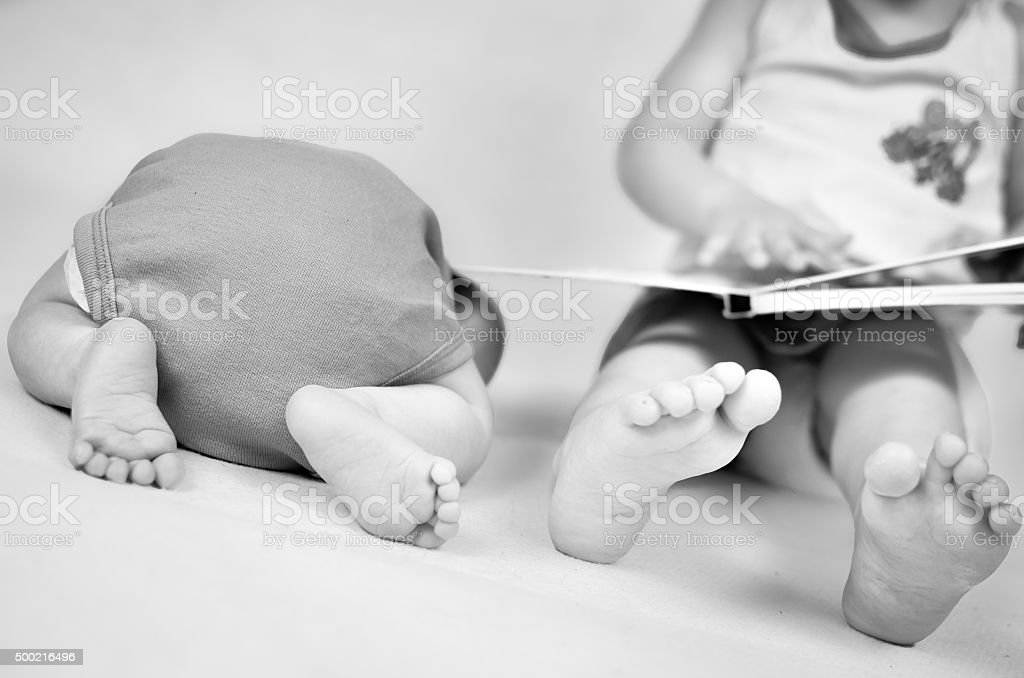 Little girl is reading a book tog her baby brother. stock photo