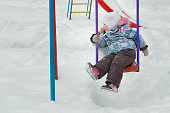 Little girl is riding on frosty winter playgrounds swing