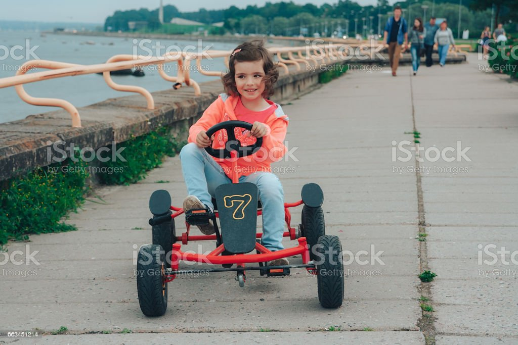 Little girl is riding on pedal karting. stock photo