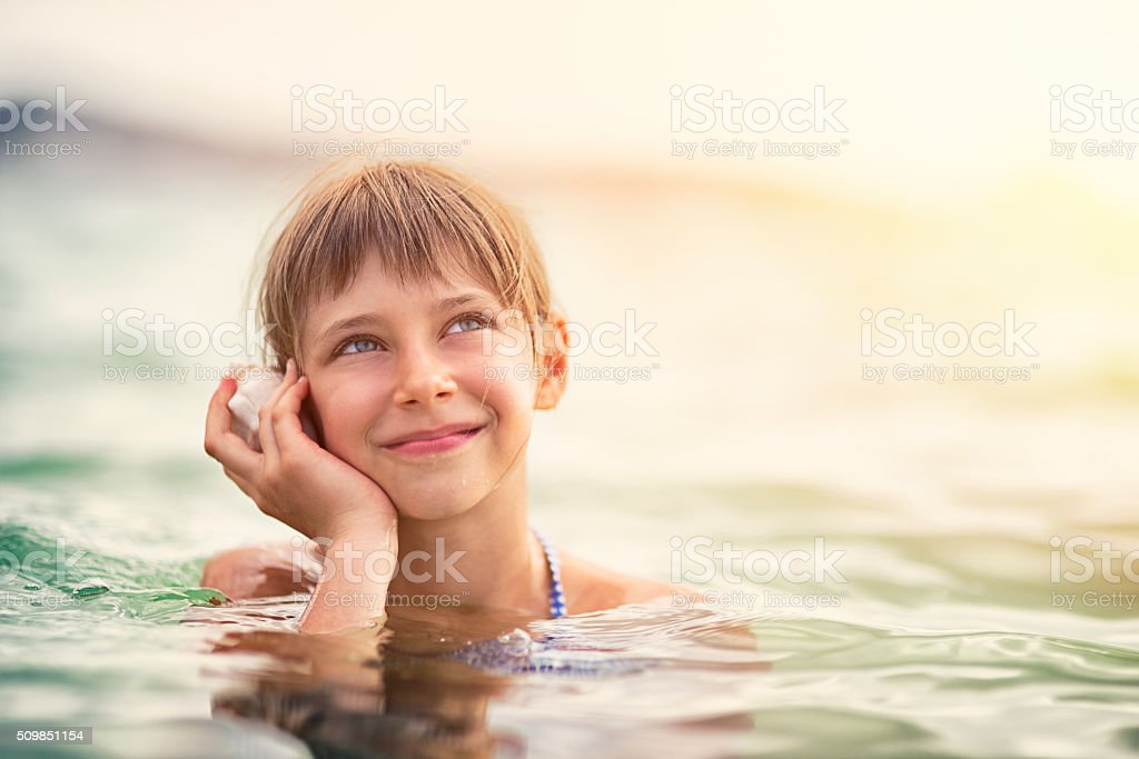 Little girl is sea listening to a sea shell stock photo