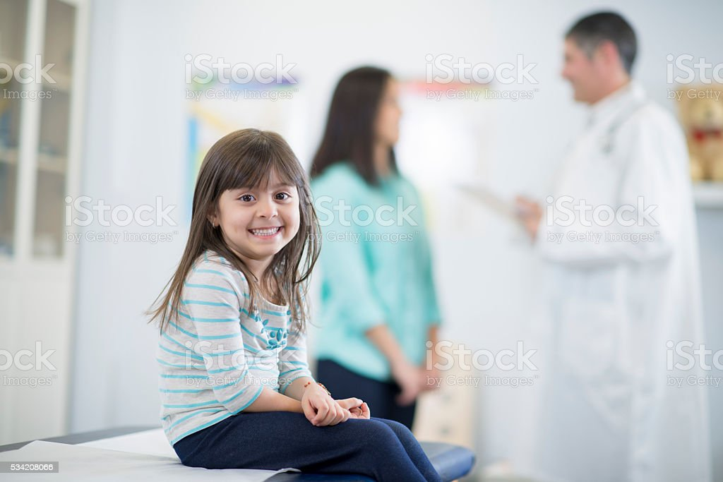Little girl is sitting on the examination table stock photo