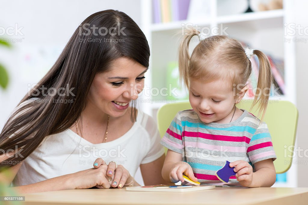 Little girl is solving puzzle. Mother watching at her actions stock photo
