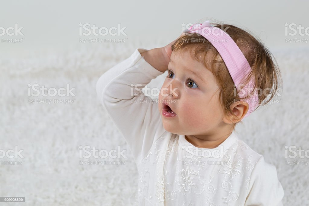 Little girl is surprised and is looking towards parents stock photo