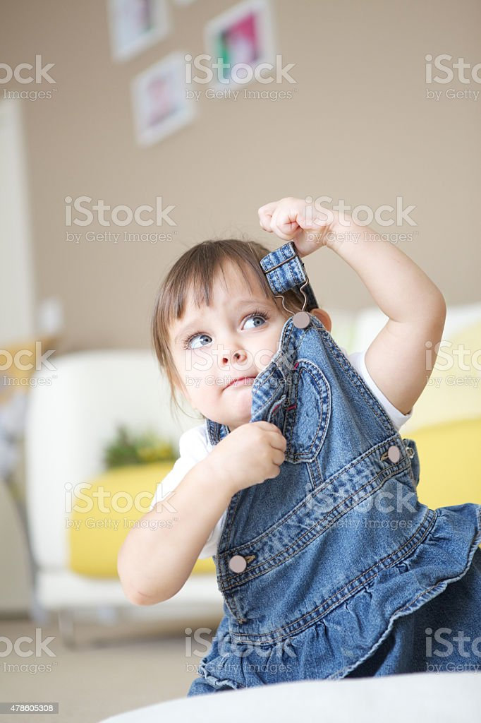 Little Girl is Trying to Remove Her Rompers stock photo