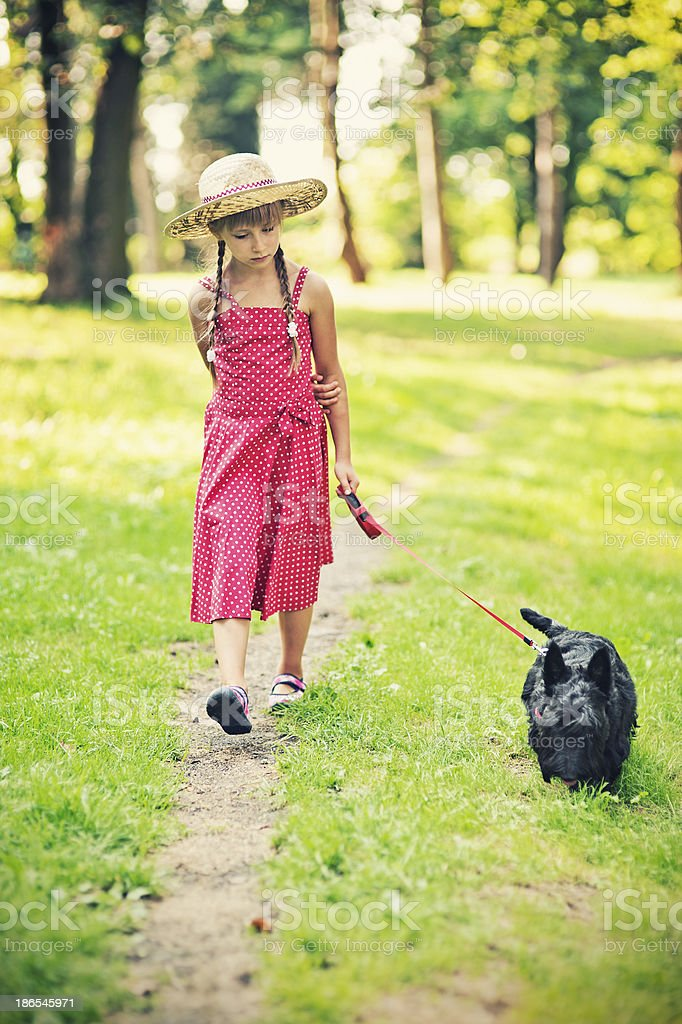 Little girl is walking her dog royalty-free stock photo