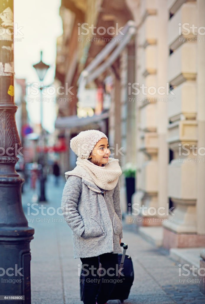 Little girl is walking with big trolley case stock photo