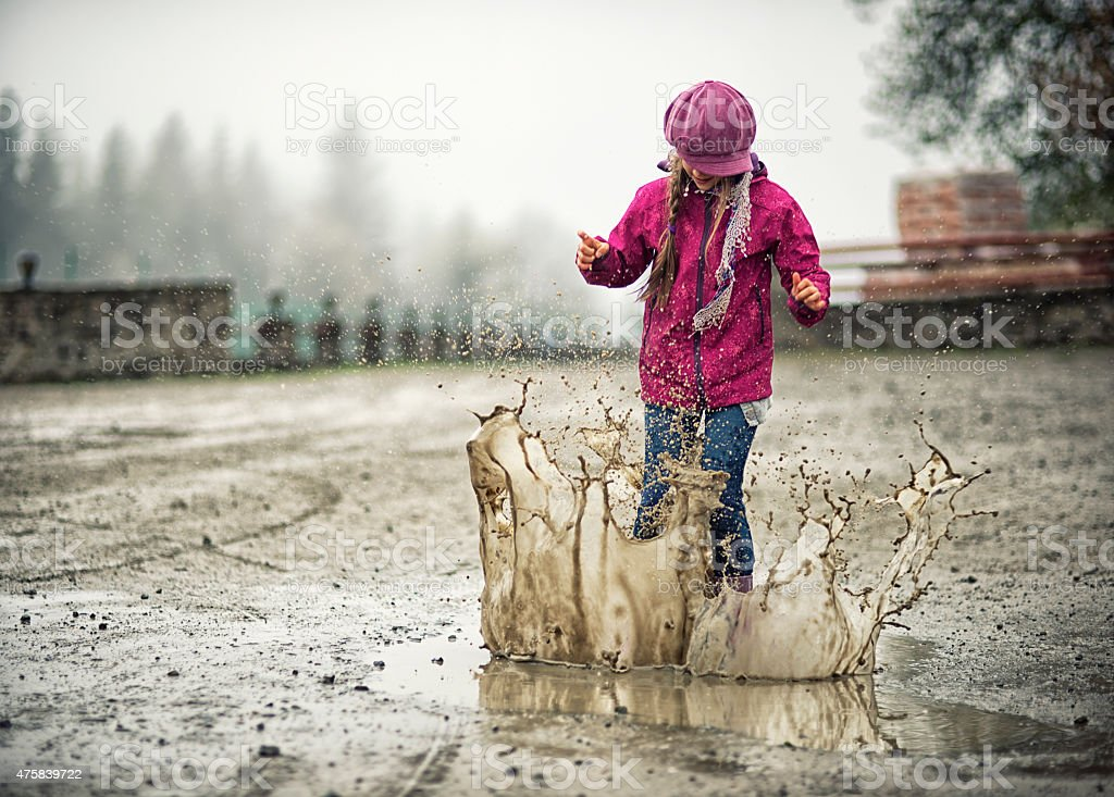 Little girl jumping in muddy puddle stock photo