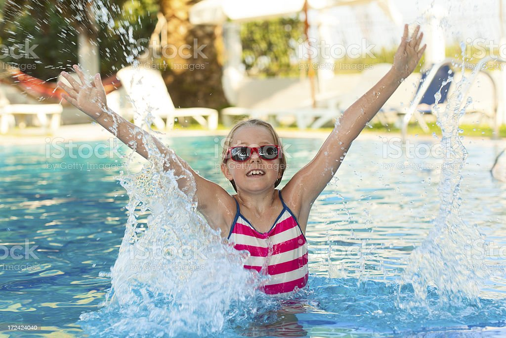 Little girl jumping in swimming pool stock photo