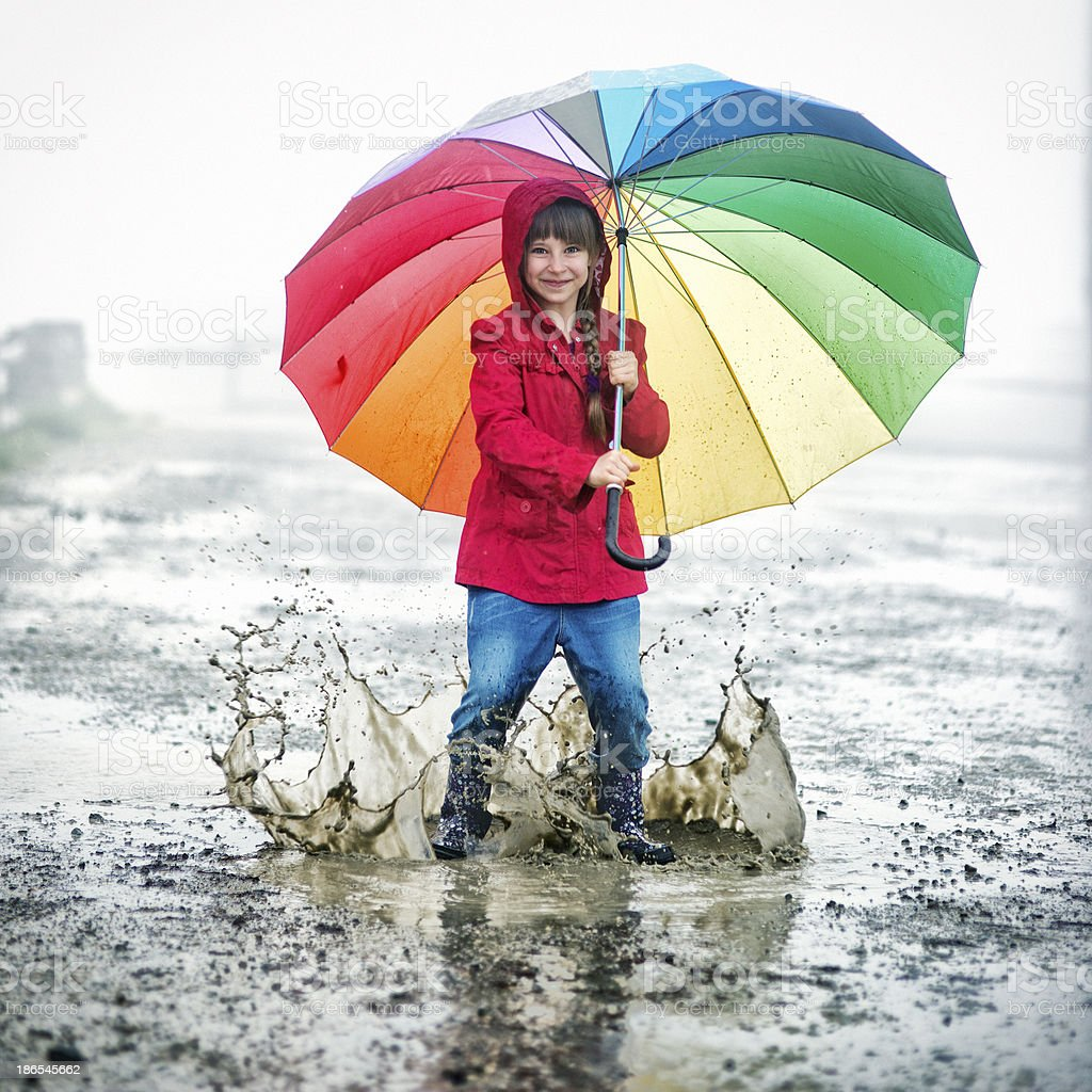 Little girl jumping in the puddles stock photo