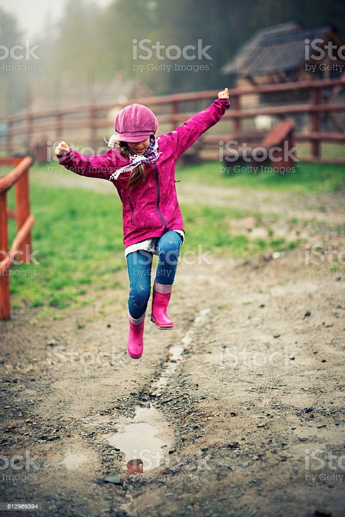 Little girl jumping into spring puddle stock photo