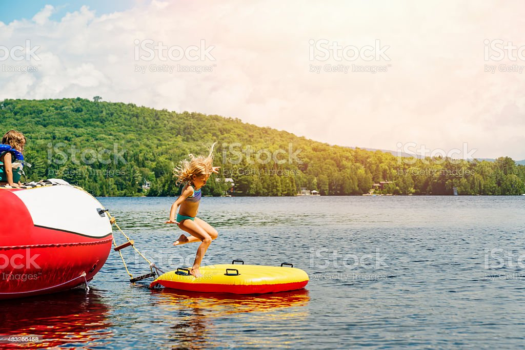 Little girl jumping on board in middle of lake. stock photo