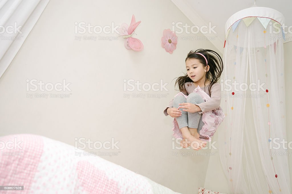Little girl jumping on her bed stock photo
