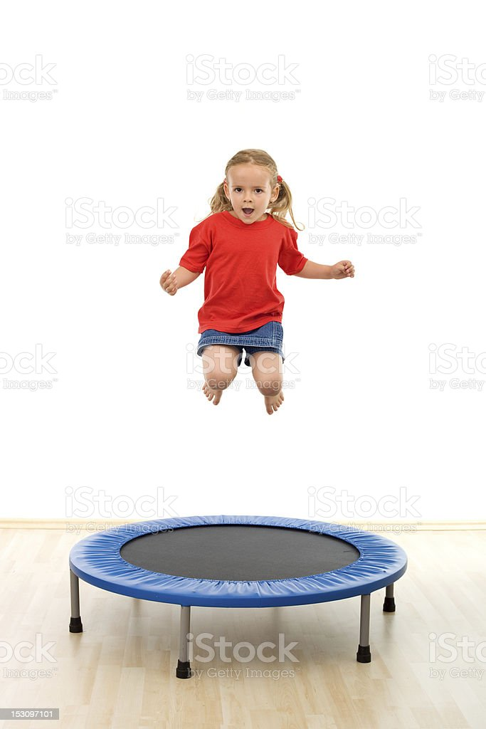 Little girl jumping on trampoline stock photo
