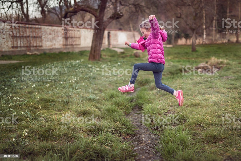 little girl jumps over a small stream stock photo