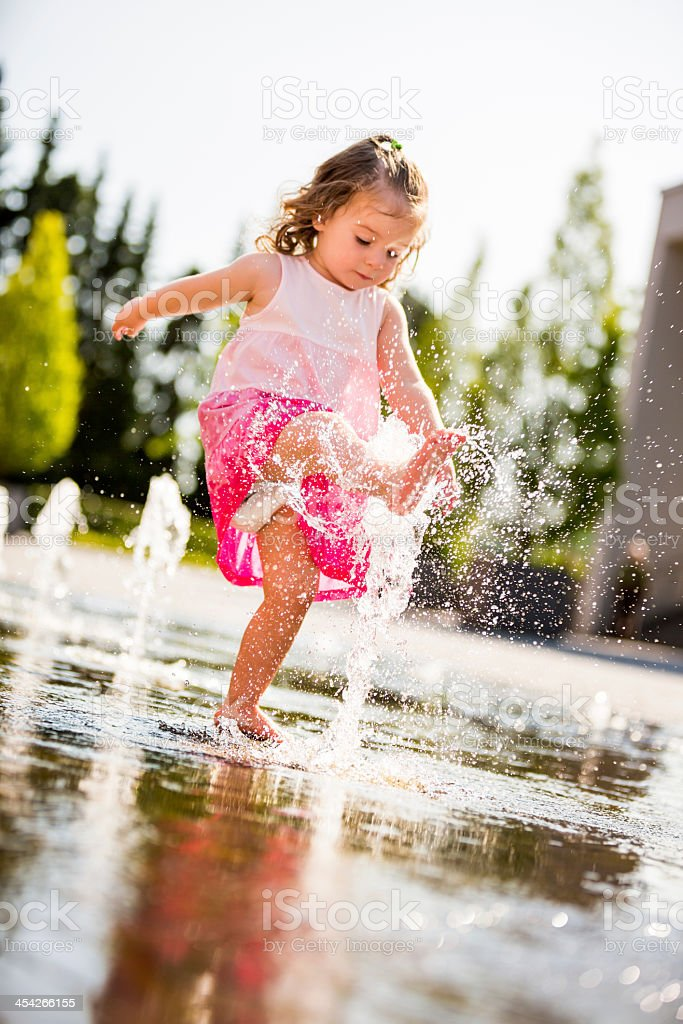 Little girl kicking water jet of fountain royalty-free stock photo
