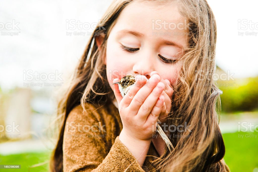 Little girl kissing a bird royalty-free stock photo