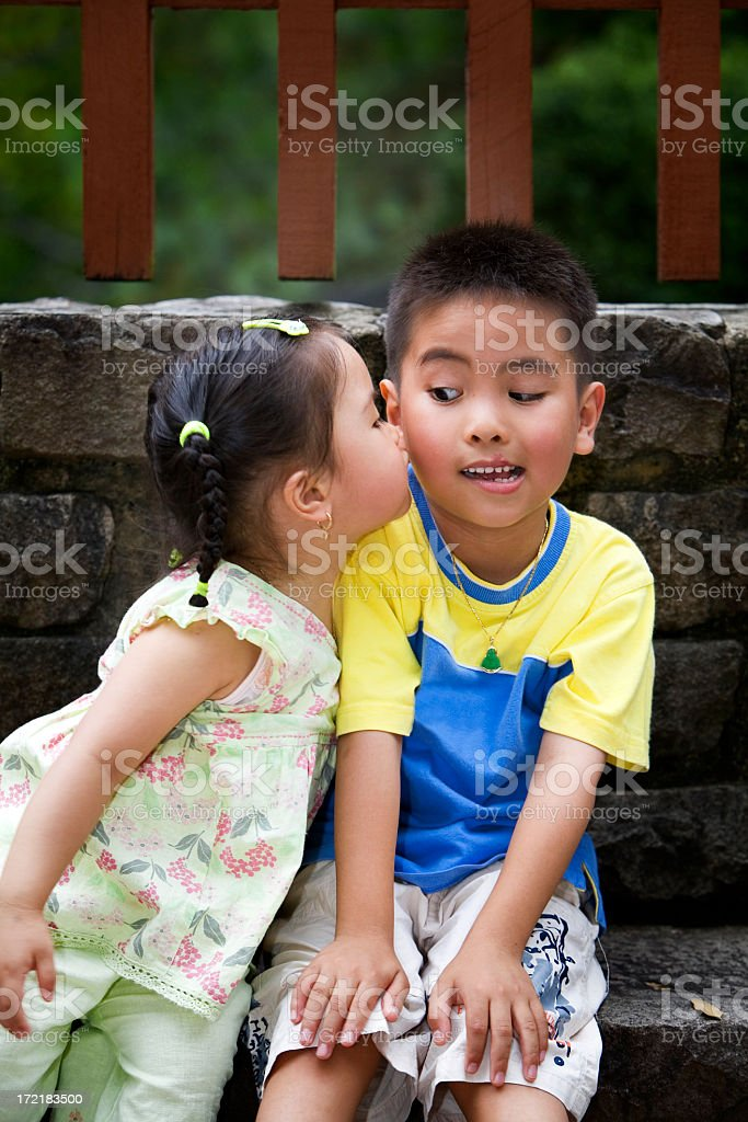 Little girl kissing a little boy's cheek without permission royalty-free stock photo