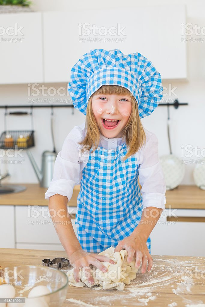Little girl kneads a dough on a table and smiles stock photo