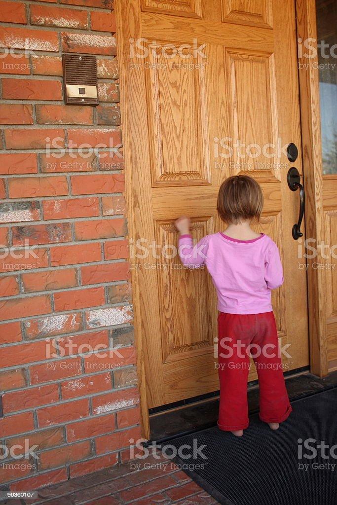 little girl knocks on large oak  door stock photo