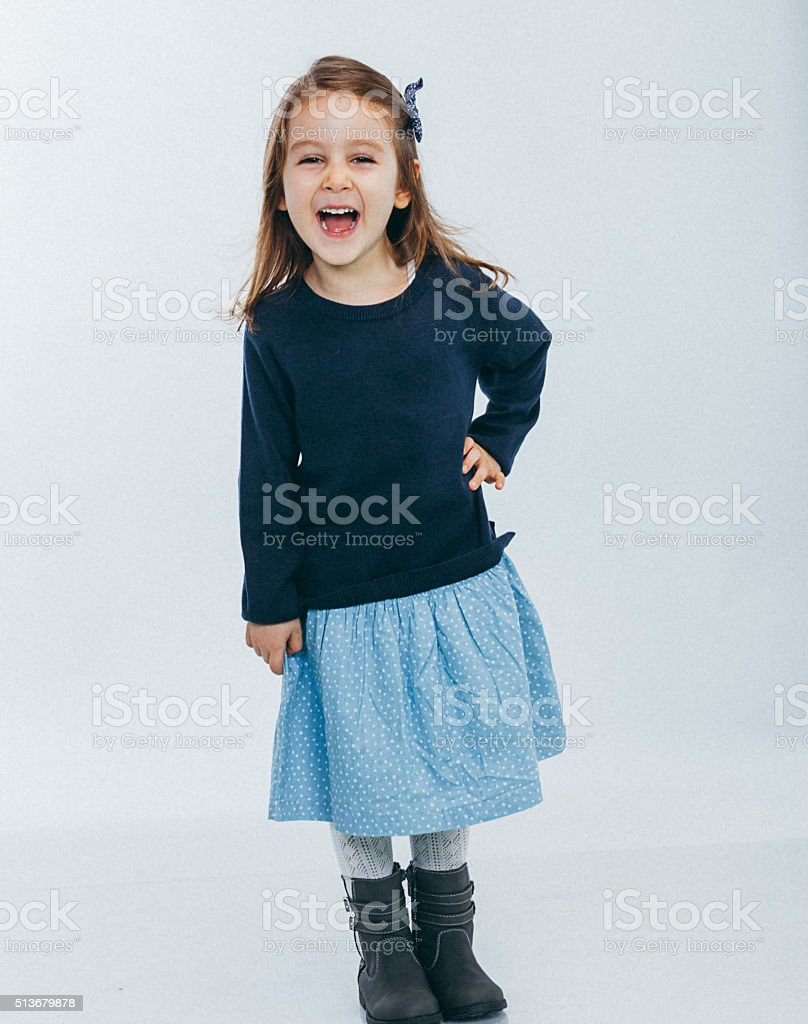 A cute happy young girl posing smiling standing over a white...