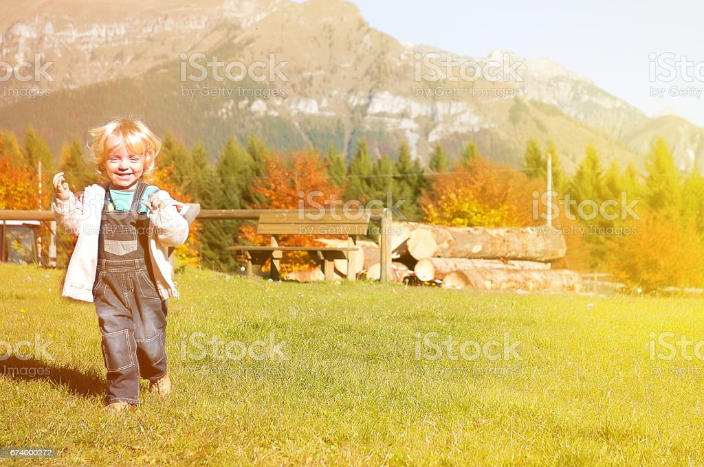Little Girl Laughing and Walking on Meadow stock photo
