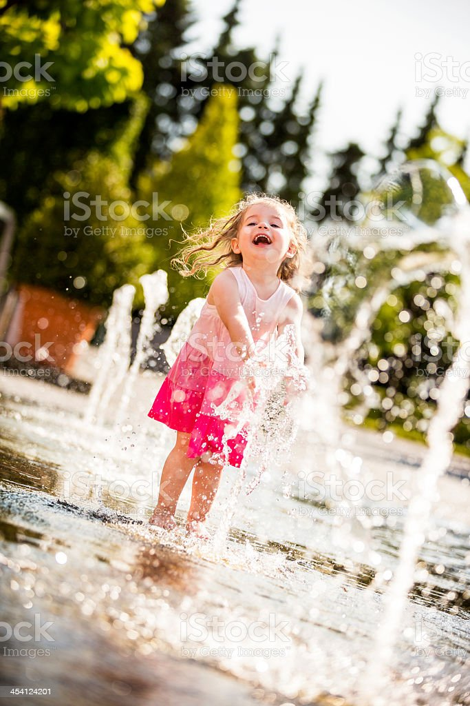 Little girl laughing while splashing water in fountain stock photo