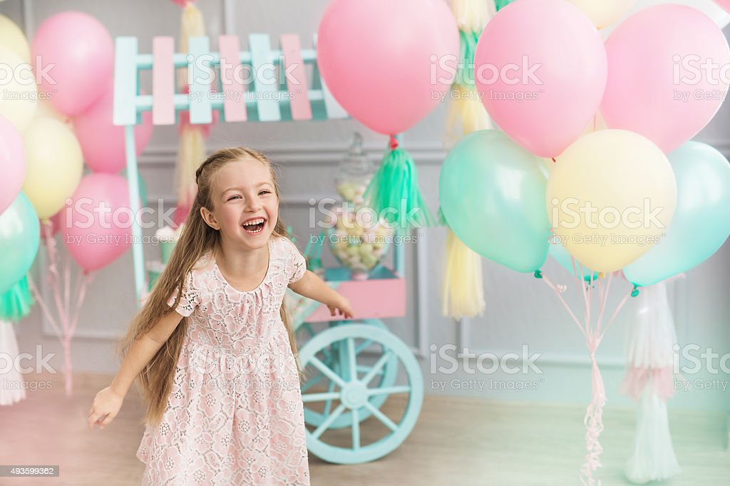 Little girl laughs in a studio decorated many balloons stock photo