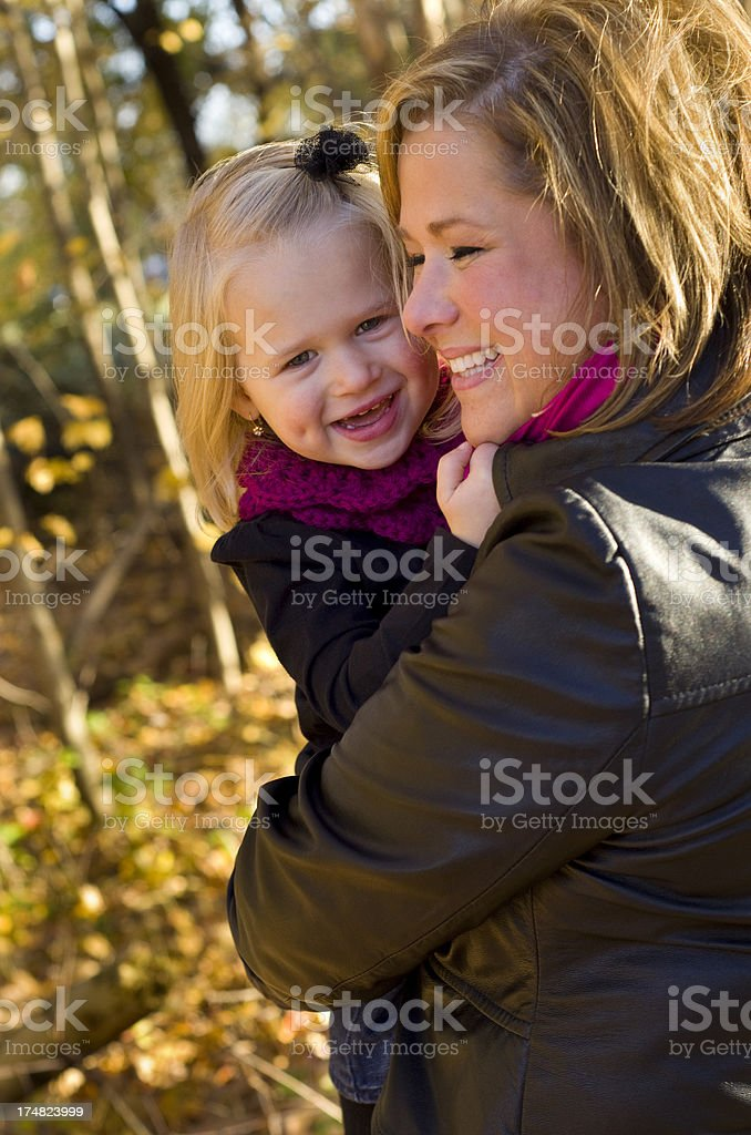 Little girl laughs with her mom in fall leaves royalty-free stock photo