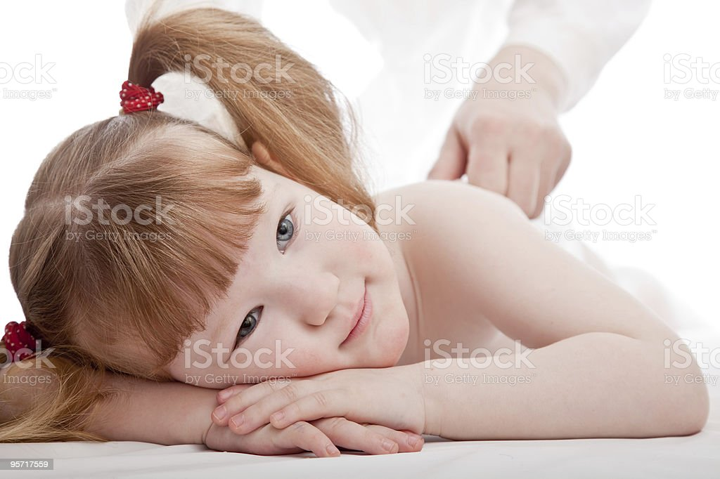 Little girl laying down with someone touching her back royalty-free stock photo