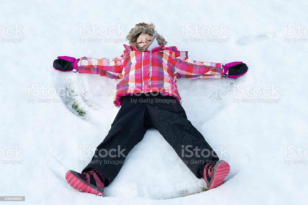 Little girl laying on snow and making angel stock photo